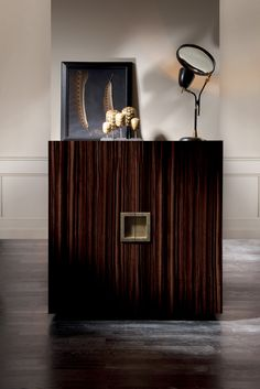 Gilbert Alto is Wardrobe by DOM Edizioni featuring two doors, two glosses and two handles, in polished brass, polished chrome or bronzed finishes. particular for longitudinal veneer it is made of real Ebony Makassar. #cabinet #wardrobe #ebony #makassar #domedizioni #domenicomula