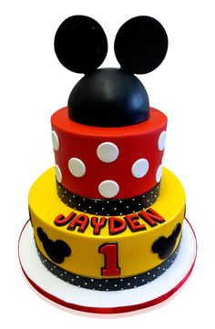 Mickey Clubhouse Birthday Cake When little Jayden turned one, we created this stunning Mickey Clubhouse cake for his event which was a large party attended by 75 people! Jayden may be too small to remember but the guests certainly won't forget! His Mickey cake stands on a white round base surrounded by a bright red ribbon. The first tier is decorated with yellow fondant and has a black stripe .... http://cmnycakes.com/gallery2/v/Cakes+For+All+Occasions/Mickey+Clubhouse+Birthday+Cake.html?