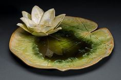 "Anne Gary -Lily pad and flower sculpted from porcelain. Crystalline glaze applied to both with flower reflecting in pooling glass crystalline glaze. Suggests melting the ""Dishing it Out"" glass plate into a hand-built ceramic plate. Hand Built Pottery, Slab Pottery, Pottery Bowls, Ceramic Pottery, Pottery Art, Ceramic Flowers, Clay Flowers, Ceramic Clay, Ceramic Plates"
