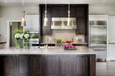 Trendy kitchen with Shaker style doors and drawers in walnut [Design: Braam's Custom Cabinets]