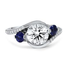 ADORNED CASCADE THREE STONE RING In this regal custom version of the Cascade Three Stone Ring, a stunning center diamond is accented by two beautiful sapphire accents and twenty-two diamond accents. Pierced filigree and hand engraved details finish this remarkable setting.