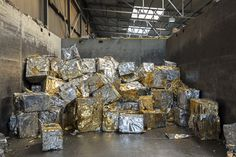 Trash Is Ugly, But Recycling Is Downright Beautiful | Scraps of aluminum are compressed into large blocks laced with golden lacquer used for beer can packaging. At a recycling smelter, the lacquer is burned and the molten aluminum is recast into new blocks that can be used to make new cans.  | Credit: Paul Bulteel | From Wired.com