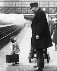 Bristol, England; May 1936  A little traveler asks for directions from a train station attendant.