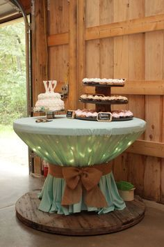 Wooden spool with icicle lights covered with round table cloth / http://www.himisspuff.com/wedding-dessert-tables-displays/12/