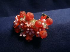 Bracelet created from 1950-1960 costume plastic flower beads repurposed onto bracelet frame with wire and covered in the back with velvet~corsage bracelet in pink and red