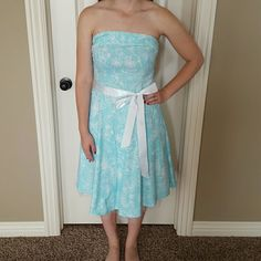 Beautiful blue strapless dress Beautiful light blue and white A line strapless dress with floral design. Has a bow that can tie either in the front or the back. Super cute! In excellent condition! Model typically wears a size 4, but this is a size 7/8 in juniors. Dresses