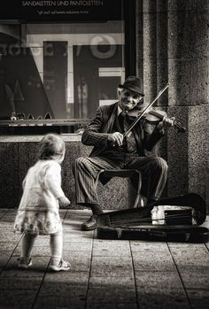 You know she's grinning :) I love how there is no prejudice, just a young girl enjoying beautiful music an old man is making :)