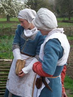 The women in this picture are wearing linen forehead cloths and coifs, linen neckcloths, woad-dyed gowns over a kirtle (the 'red' kirtle dyed with madder), and linen aprons. The woman on the left has linen oversleeves; the woman on the right wears a linen partlet. Both women have leather pockets attached to their girdles.