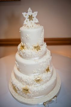 Ivory and gold winter themed wedding cake wrapped in snowflakes by Corr's Cakes
