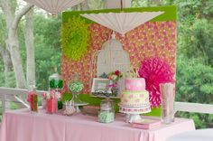 The dessert table was created using Lilly Pulitzer wrapping paper on the backdrop as inspiration and tissue paper fans and paper parasols. The vintage bird cage added a nice touch.