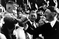 Adolf Hitler shaking hands with a young boy, c. 1932.