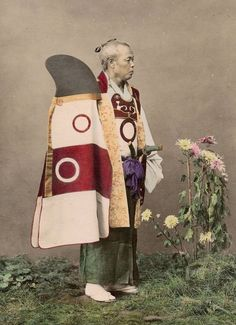 Retired samurai with a kaji zukin and shikoro (fire hood and cape), a samurai fire costume.  Hand-colored image.  Unknown photographer.  About 1880's, Japan. The Kimono Gallery