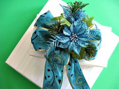 Blue glitter Christmas bow with blue peacock ribbon via Etsy.