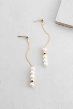 Classy pearl dangling earrings with accents of magnificent gold. A sleek and beautiful drop earring.