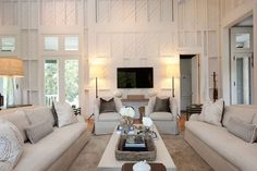 Fantastic living room with painted wooden plank board walls. Neutral linen slipcovered sofa and armchairs. Mink colored area rug white coffee table with woven tray and flower vase. Wall mounted tv console table and iron floor lamps. - June 15 2019 at Style At Home, Living Room Colors, Living Room Decor, Living Spaces, Monochromatic Living Room, Best Wall Colors, White Wood Paneling, Custom Wood Doors, Highland Homes