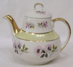 """Very pretty teapot from Gibson and made in England. Pink flowers around sides and a pale yellow band trimmed in gold. Measures 7"""" in height and 8"""" spout to handle. No cracks, chips or hairlines. Favorites List ! 