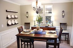 Such a gorgeous dining room. I love that there isn't a whole lot of fuss: the left wall's wall art is the fancy dinnerware, the other wall has 4 simple mirrors and the table is set for 2. I think it's nice that the centerpiece (natural yarn) and the branches on the buffet can stand out.
