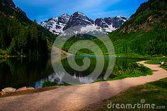 Infamous Maroon Bells of Aspen Colorado with Walking Path and reflection  A perfect early summer day with morning sunrise sunshine and crater lake with a nice lake reflection and even the walking path with no one in site.