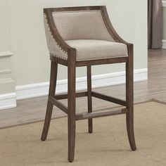 When a well tailored look, without being formal is what you desire, the Cormiers Stool is the perfect fit. The solid birch wood frame features a warm brown distressed finish to complement the light beige linen look upholstery. Antique brass nail head accents adorn the outside back and arms with welting accents on the inside back and seat cushion. The metal kick plate protects the comfortable foot rail and adjustable leg levelers ensure stability.