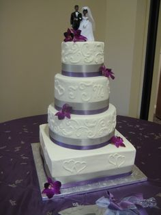 Four tier square and round wedding cake with purple and gray ribbon and fresh flowers. Decorated with scrollwork and hearts.