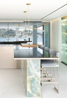 Blue Onyx feature on the kitchen island with matt brass pendant lighting feature. Luxury modern duplex penthouse in Istanbul, Turkey designed by 1508 London. Project Esra. Designs featured on www.martynwhitedesigns.com
