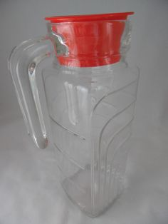 The correct way to store water or orange juice in your refrigerator is found in this delightful, slim, space-sqaving Orange Juice Pitcher made of clear ribbed glass with a bright red lid  - did I mention it is a Space Saving Juice Carafe?#Lilac