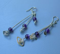 sterling silver and gemstones lond dangle drop earrings. This cute young and fun pair of earrings is handmade of sterling silver and semi precious stones. They are handcrafted using hand tools only and may differ slightly from those in the picture. These earrings are sculptured from 19 gauge sterling silver wire, hammered out for hardness & shape. They are hard and sturdy and made to last. you can order these earrings with the choise of: Turquoise Garnet Amethyst white pearl pink pearl ...