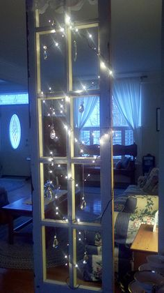old window used as a room divider- string with mini lights and prisms!
