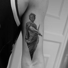 Julius Caesar tattoo on the left bicep.