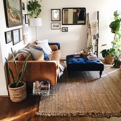 Leather sofa, beautiful blue ottoman,  a sisal/ jute rug, and a gallery wall. Relaxed warm living room.
