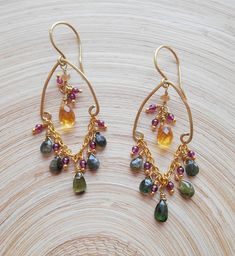 Bold and regal, elegant and modern, Twinkle chandelier earrings have a festive, cool-toned color story and lots of sparkle! I hand formed and lightly hammered a petal shaped frame out of gold filled wire and I suspended a fiery faceted citine drop from the top of this frame. Five