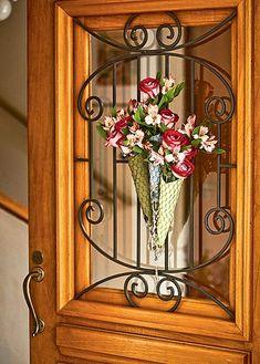Na porta de entrada, Claudia Regina, da La Calle Florida, fez um buquê com rosas e astromélias envolvidas em guardanapo e tela de galinheiro. As espécies de flores são baratas