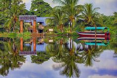 River Reflections along the Suriname River in South America. Caught the palm trees,the wooden house and colorful fishing boat in the stillness of the water.