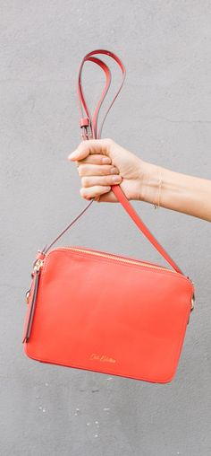 A stylish lozenge-shaped cross-body bag with two zipped compartments, each with internal pocket and Island Bunch cotton lining, and an adjustable cross-body strap. In premium cherry red leather with gold tone hardware to complete the look.