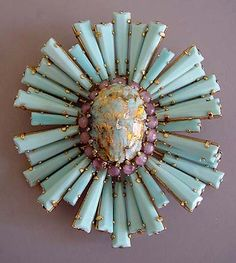A vintage sunburst brooch made from an oval cabochon, pink rounds, and light turquoise faceted keystone rays.