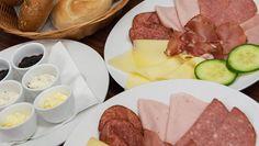 reichhaltiges Frühstück, frisch aufgelegte verschiedene Wurstsorten, mit Käse und Gemüse.