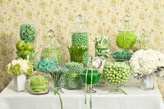 Green and serene, this green candy buffet both sweet and trendy White details - flowers and cookies - add visual interest. Buffet tip: Including color-coordinated fruit (like apples!) in your candy buffet is a nice treat for guests who enjoy a break from candy.
