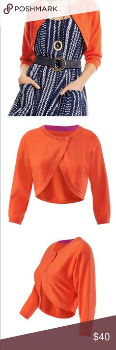 "CAbi Piccolo Shrug. Size XS Brand new, perfect condition CAbi Piccolo shrug in TigerLily (Orange). Double button front, cropped with 3/4 length sleeves. Inside has a contrasting purple ribbon lining neck for an additional pop of color. Soft and easy to wear with rounded hemline in the back. 100% cotton, measures 15"" in length from shoulder to hem. Worn once for only a couple of hours. CAbi Sweaters Shrugs & Ponchos"