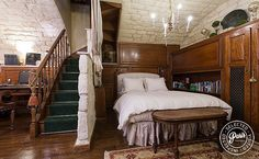Accessed by a circular wooden stairway, the basement level rooms are very private and include the second bedroom and bathroom. These rooms feature original vaulted stone ceiling arches and uniquely shaped. The bedroom has a full-size bed with wooden closets and bookshelves, and the bathroom has curved stone walls, custom washbasin, shower, and WC.