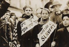 """""""Two girls wearing banners with slogan """"ABOLISH CHILD SLAVERY!""""  In English and Yiddish USA - New York, 1 May 1909"""