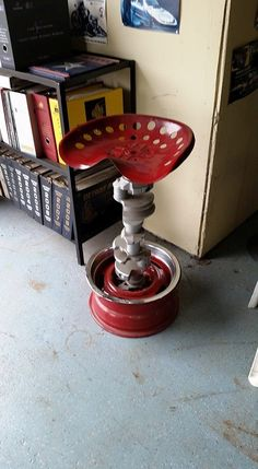 Custom gearhead stool made from a tractor seat on an engine crank shaft and steel wheel.