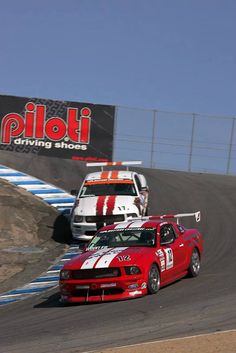 A brace of Mustang Boss 302 racers plunging down the Corkscrew at Laguna Seca - Courtesy of Ford Racing