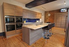 Island kitchen with seating in a soft grey acacia laminate that beautifully compliments the decor, accented with a bold blue splashback to complete the look.