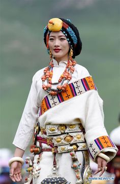A model presents traditional Tibetan costumes during a fashion show held at Batang grassland of Yushu City of Yushu Tibetan Autonomous Prefecture, northwest China's Qinghai Province, July 26, 2016.