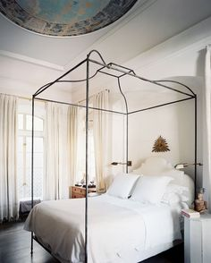 An iron canopy bed is outfitted in white sheets and an upholstered white headboard.