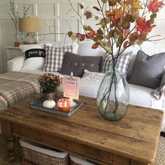 Simple fall decorating with autumn branches and leaves in a large demijohn glass vase on a rustic, reclaimed wood coffee table, accented by white pumpkins and gray flannel throw pillows. Country cottage style decor.