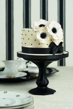 I adore this little single layer cake with the black dots and the ribbon at the bottom for detail.  The flowers are a perfect finishing touch.  Such an adorable cake!   ᘡղbᘠ