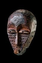 """Small face mask """"mbuya"""" D. R. Congo, Pende wood, blackish brown patina, camwood powder, of triangular form with a slightly bulging forehead and flattened facial plane, the lower half coated with drilled holes, castagnet eyes with pierced pupils, slightly dam. (nose), missing parts (backside at the rim), drillings along the rim backside partly broken  H: 20,5 cm    Read more: http://www.tribal-art-auktion.de/en/catalogue167/d20_361/#ixzz3L3kufrrH"""