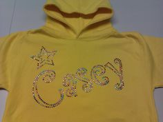 Casey hoodie, written in the bubbly Curlz font with a pretty star above the name. All done in the multicoloured rhinestuds on a sun yellow hoodie. This kind of product can be fully personalised with different fonts/designs and colours of diamontes. For more info please visit our website or give us a call!