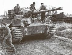 A captured Tiger 1 tank being inspected by British troops with a burned out Panther V in the background